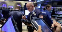 FILE - In this Sept. 18, 2014, file photo, trader Damian Bagarozza, center, works on the floor of the New York Stock Exchange. On Sept. 18, the U.S. stock market was at a record high after a relatively uneventful summer. Long-term interest rates were heading higher, a sign that investors expected steady growth in the U.S. economy. (AP Photo/Richard Drew, File)