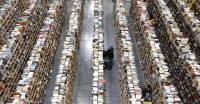 FILE - In this Dec. 2, 2013, file photo, Amazon.com employees work the shelves along the miles of aisles at an Amazon.com Fulfillment Center on